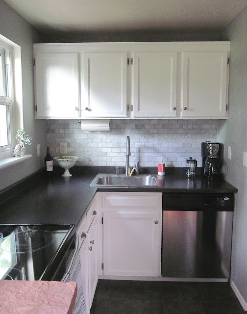 Lovely small kitchen with black laminate countertops and marble backsplash