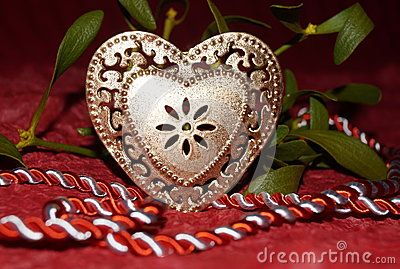 Golden heart and mistletoe on red background