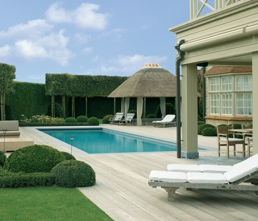 I love the topiary and tall green privacy hedge around this pool