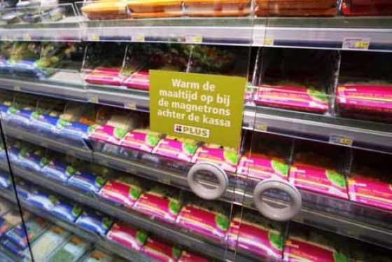 De sticker op de koeling met kant-en-klare maaltijden wijst op de magnetron in het zitgedeelte waar klanten de maaltijd ook kunnen nuttigen.