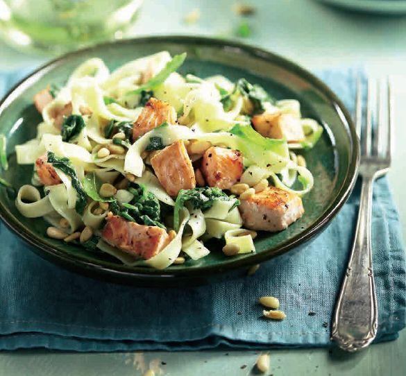 Kook de pasta beetgaar. Besprenkel de zalm met citroensap en bestrooi met zout en peper. Verhit 2 eetlepels olijfolie en bak hierin de zalm in 2-3 minuten rondom lichtbruin. Schep de zalm uit de pan en houd warm onder aluminiumfolie. Fruit de sjalotjes en knoflook circa 2 minuten in het bakvet. Voeg de rest van de olijfolie en spinazie toe en roerbak totdat de spinazie iets geslonken is. Rooster intussen de pijnboompitten in een droge, hete koekenpan goudbruin. Meng de helft van de ...