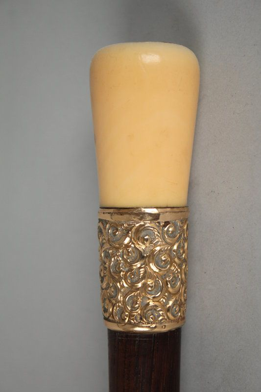 inely carved whale ivory handle walking stick with hardwood shaft, 19th century, ornate brass collar, a Roman medallion or coin is mounted on the top of ivory handle. Size: 35 inches in length. Condition Report: great condition.