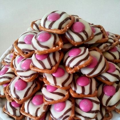 I make these very year. Place unwrapped hugs on pretzels. Place in oven at 200 for 8 minutes or until hugs look shiny. Take out and then quickly yet carefully put v-day m&m on each one. Place in fridge for 20 minutes. Then voila! Pure yumminess!!! PERXFOOD.COM
