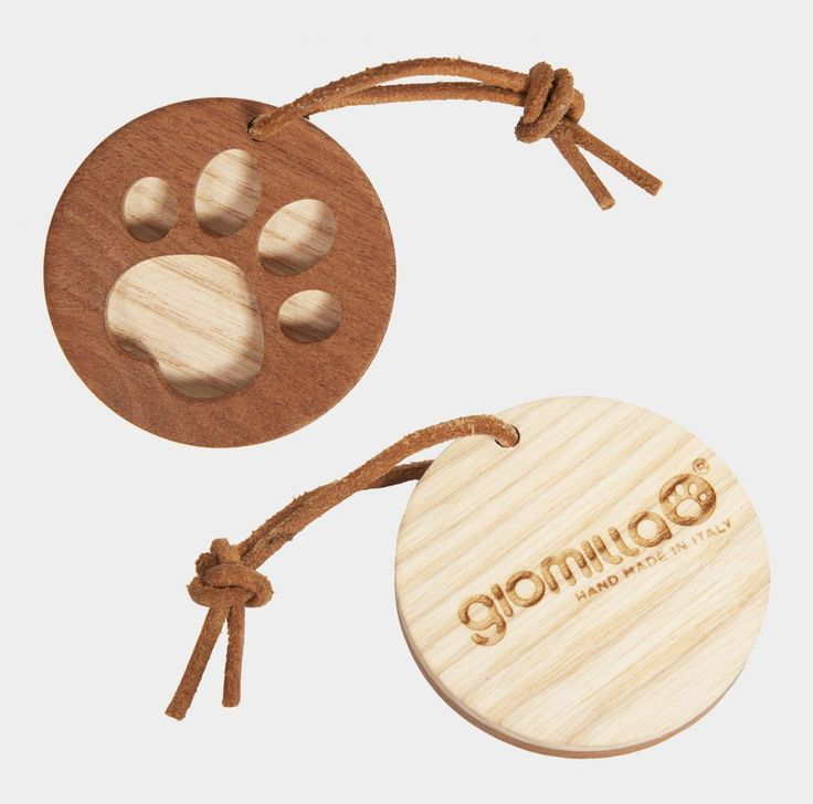 """The Giomilla's keyring. Made like a """"biscuit"""" of two piece of solid wood (one for side), it's the same paw logo on the front side of the houses, with a laser engraved Giomilla's logo on it's back side, and with an eco leather string for hang it."""
