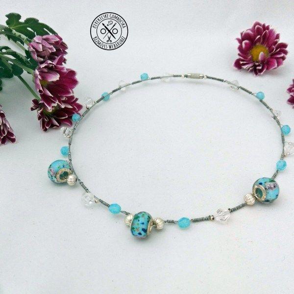 Merev nyaklánc lámpagyöngyökkel - 2790 Ft  Rózsamintás lámpagyöngyökkel, antikolt ezüstszínű hordókkal, kék és áttetsző elemekkel díszített, dróttal fűzött, szép tartású nyaklánc. A nyaklánc átmérője: 14,4 cm