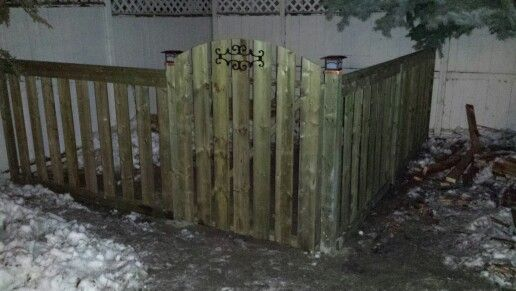 Dog run in pressure treated wood and arched gate with Decorative Feature and solar post caps.