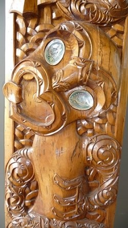 Maori Tiki Wood Carving     first man, fertility symbol     A Tiki wood carving with typical characteristics such as paua shell eyes, the tilted head, a jutting tongue, the traditional three fingers on each hand and spiral shaped (koru) patterns