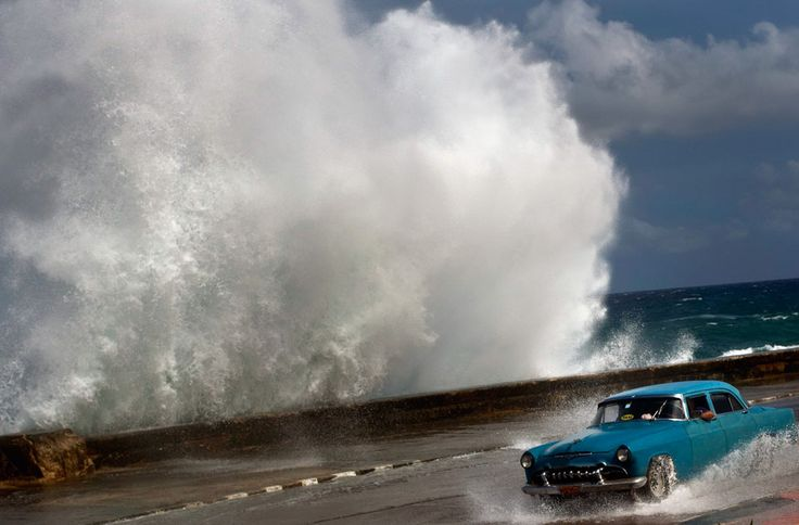 A driver maneuvers his car along a wet road as a wave crashes against the Malecon in Havana, Cuba, on October 25, 2012. Hurricane Sandy blasted across eastern Cuba on Thursday as a potent Category 2 storm and headed for the Bahamas