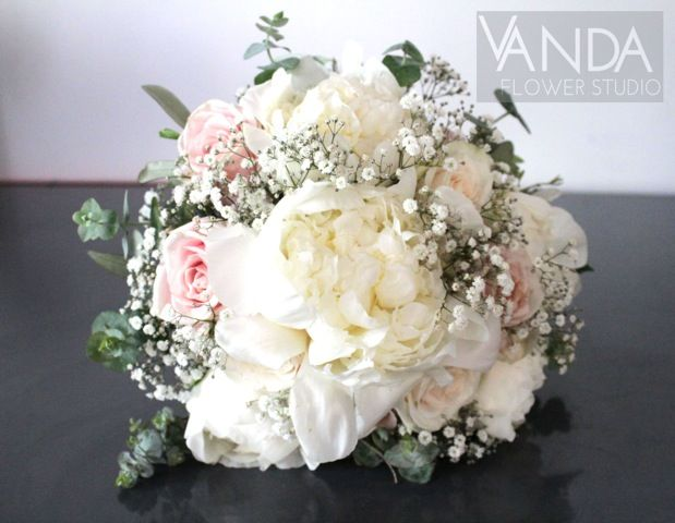A fluffy, romantic bride's bouquet of cream Peony, cream and blush pink Rose, and Gypsophila, framed with Eucalyptus tips and sprigs of Olive.