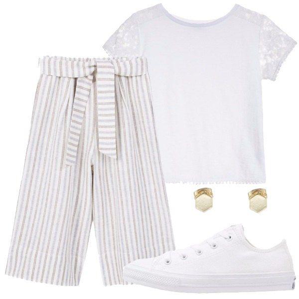 Degli splendidi tessuti per questo outfit: lino e viscosa per il bel pantalone a fondo bianco, fantasia a righe e vita alta e cotone per la t-shirt con maniche in pizzo. Abbiniamo delle sneakers bianche e orecchini a lobo.