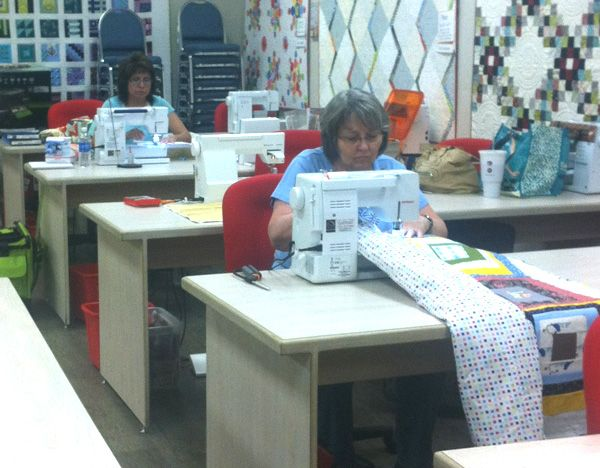 Students learning how to machine quilt on regular sewing machines