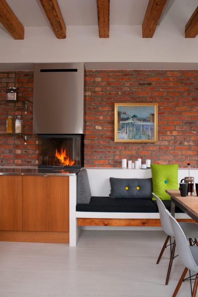 EKSPONERT TEGL: Et betydelig veggparti fra bygningens indre er blottlagt. De snart hundre år gamle mursteinene er brent litt ulikt, og har derfor samme røffe karakter som bjelkene. Vedovnen fra Spartherm er i kjøkkenbenkhøyde slik at man har innsyn til flammene nesten uansett hvor man befinner seg i rommet.