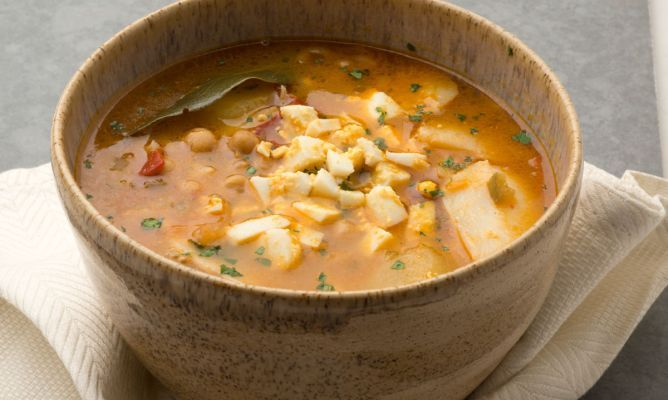 Receta de Karlos Arguiñano de guiso de bacalao con garbanzos, patata, huevo cocido, fideos, cebolleta, pimiento y tomate, un plato saludable y sencillo de preparar.