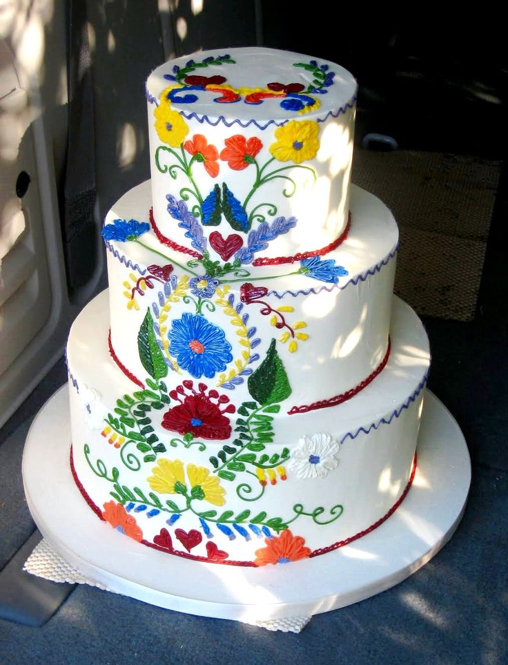A Mexican themed wedding cake. Looks like the embroidery on Mexican dresses and blouses-very colorful !
