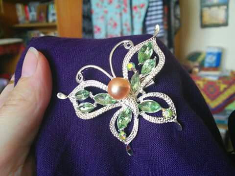 Silver-colored butterfly brooch with pastel green stones and freshwater pearl.  https://www.facebook.com/groups/beautiful.indonesia.kiegeszitok/