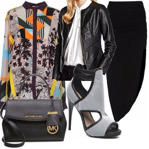 Si può osare con i colori quando c'è il nero che sdramatizza. Camicia colorata in tonalità nero arancione giallo e azzurro con uno sfondo grigio chiaro, gonna lunga con spacco laterale, borsetta piccola a mano e sandali alla caviglia in rete.