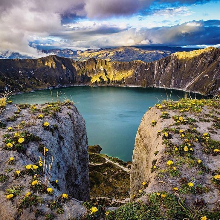 Laguna de Quilotoa, Ecuador. The crater lake of Laguna Quilotoa is nestled 3,800m high in an active Andean volcano. Located about 100 km south of Quito, the 'Laguna,' or lake, sparkles a beautiful emerald colour due to high mineral content in the icy water. The surrounding area offers stunning vistas with high mountain peaks and rugged Andean landscapes.