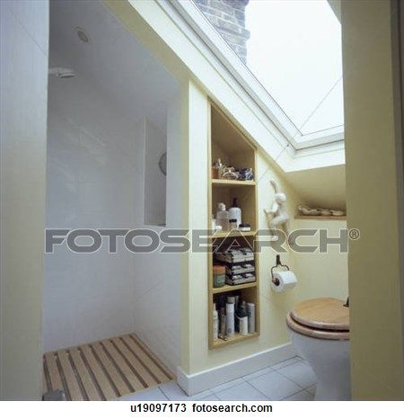 Velux window above toilet in small attic bathroom with open shower and recessed shelving View Large Photo Image