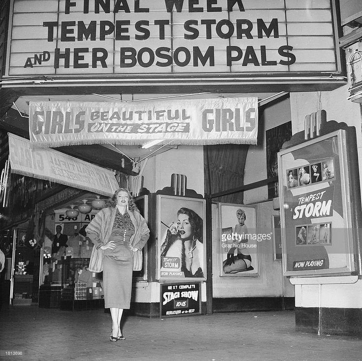 American stripper Tempest Storm poses under a theater marquee for her burlesque act, 1954. The marquee reads: 'Final Week/Tempest Storm and Her Bosom Pals.'