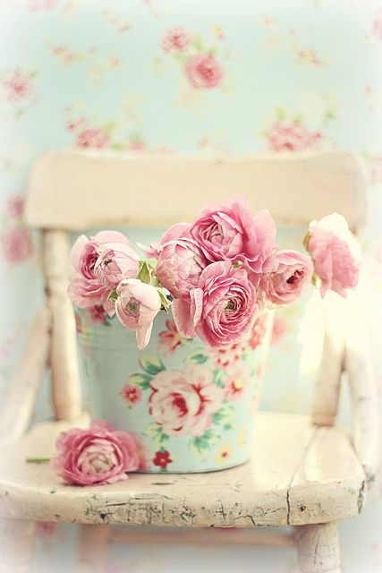 ..how beautiful...the old worn chair..floral pail with pink roses...AND the wallpaper!!!!!!!!!!!!!!!!!