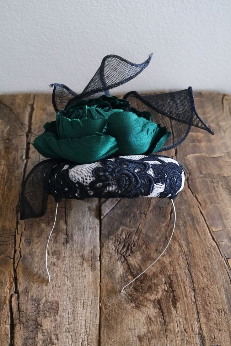 Courchevel Race ready and incredibly gorgeous this fascinator is an elegant and dramatic piece. The key feature is a hand crafted emerald green silk dupion rose, surrounded by delicate navy  sinamay tendrils, atop of a black French guipure lace & ivory sinamay pillbox.