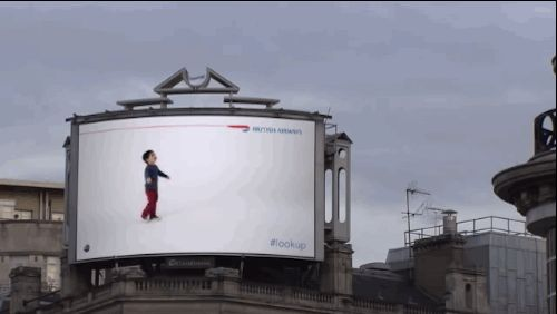 A British Airways billboard features video of a kid pointing to an actual plane in the sky and gives its flight info.