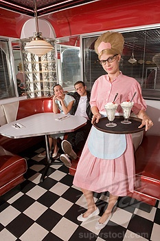 Waitress in 1950s style uniform serving ice cream sundaes to couple in diner 17857950