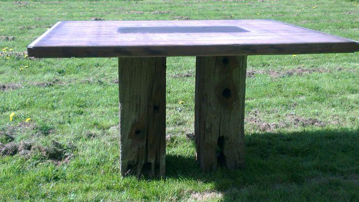 Een exclusieve tafel gemaakt van eiken meerpalen als onderstel en een blad van steenschotten met in het midden gegoten granito. Zie http://www.kunstateliergina.nl/gallery/7646/Exclusieve_Tafels/