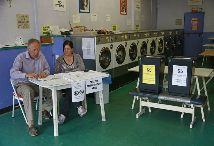 Poll clerks are seen in a public launderette being used as a polling station in Oxford, southern England May 22, 2014. Britain's anti-EU UKIP party will likely top European elections on Thursday or come a close second, according to opinion polls that suggest a barrage of criticism accusing it of racial slurs and bigotry has failed to put off voters.