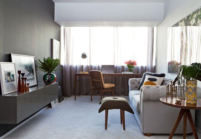 O arquiteto Robert Robl não abria mão de ter um escritório no apartamento de 40 m². Para isso, o profissional fechou com vidro a varanda de 4 m² e fez seu home office no mesmo ambiente da sala, com uma mesa de madeira imbuia