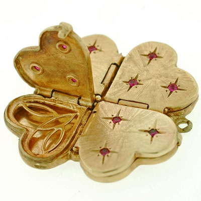 A wonderful and very unusual compartment locket from the 1950's era! This beautiful locket has the shape of a 4-leaf clover which is formed by 4 individual hearts. Made of 14kt yellow gold, each of the heart faces open to reveal a small compartment. The surface of each has a simple etched design and 3 vibrant rubies which are set within a small starburst design.