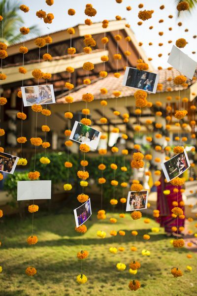 What a fabulous way of creating a photo wall - making use of marigold flower hangings as backdrop and putting up photos randomly. This is such a unique idea! Absolutely love it!