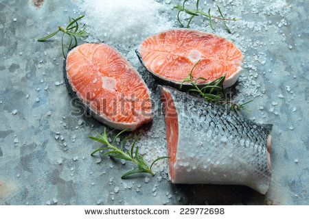 Salmon fillets with salt and rosemary on old metal board - stock photo