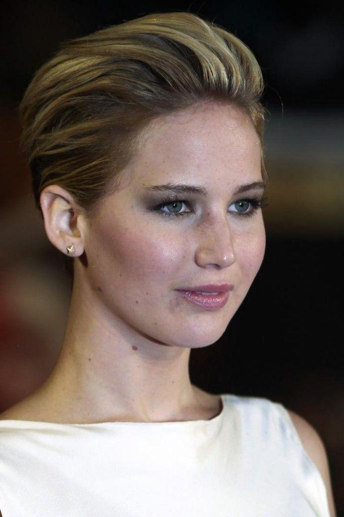 Sur cette photo, le visage de Jennifer Lawrence est complètement dégagé puisque ses cheveux courts ont tous été coiffés vers l'arrière. La nuque est très courte, mais le reste de sa chevelure comporte de belles longueurs, les cheveux n'ayant presque pas été dégradés. On remarque des mèches plus pâles dans la coloration, ce qui adoucit légèrement l'ensemble.