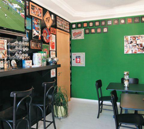 Cores escuras cobrem as paredes. A principal recebeu tinta preta brilhante (Suvinil) e as laterais, o sugestivo tom verde irlandês (Coral). O piso laminado de tom claro (Pátina Branca, da Durafloor) equilibra o conjunto. No lugar do rack, há um balcão (3,50 x 0,40 m) com armários (Marcenaria Bonaldo, R$ 2 880). É ali onde fica a TV de LCD de 40 polegadas, da Sony.