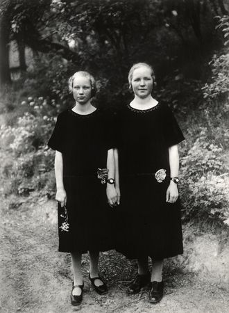 """""""In the photograph, """"Country Girls,"""" 1925, two sturdy blond girls stand stiffly before the camera holding hands and wearing identical dark dresses and watches. It seems safe to assume they are sisters, so closely do they resemble each other in appearance, expression and manner. Indeed, their similarity and closeness is as disquieting as a Diane Arbus photograph, for their dark dresses visually give the impression of one large shape with two heads emerging from it."""""""