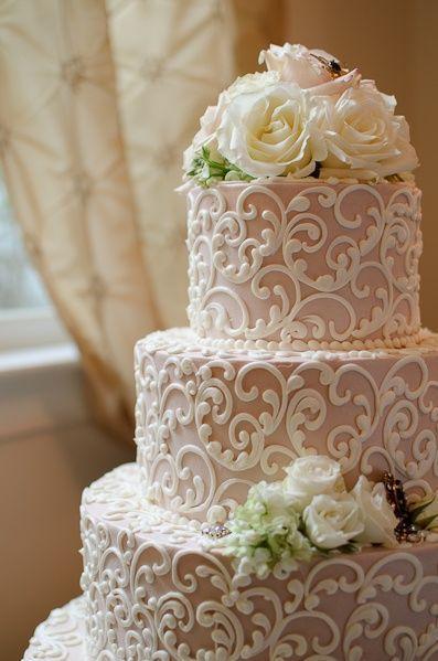 Un pastel de bodas alucinante con intricados dibujos inspirados en el vestido de la novia. Las flores naturales le dan un toque romántico.
