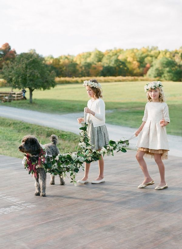 If you include young children in your wedding party, a little stage fright is a possibility especially with a larger crowd. Calm the nerves of your flower girl or ring bearer by allowing your fluffy BFF to walk them down the aisle. Rather than flower petals, decorate your dog's leash with your wedding flowers for the flower girls to hold instead.