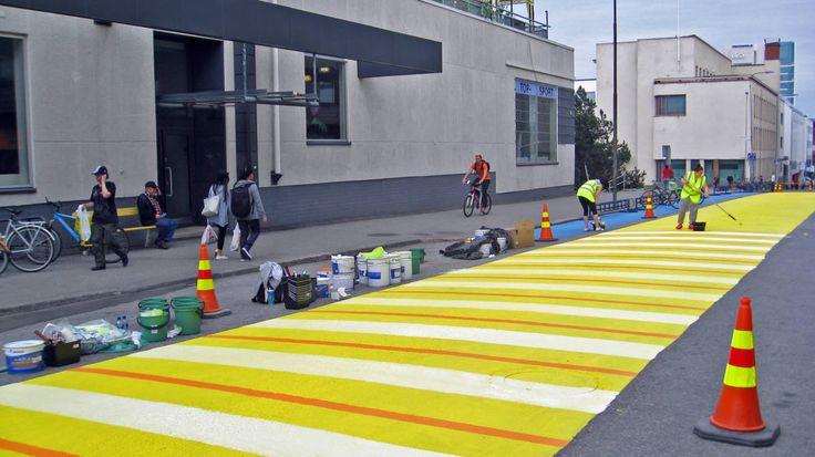Opiskelijat maalaavat taiteilija Juhani Petäjämäen suunnittelemaa räsymattoa Jyväskylän Väinönkadulle.