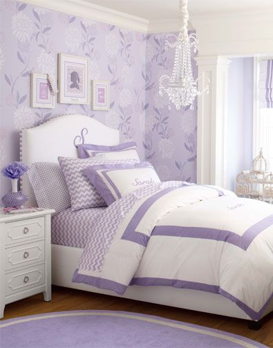 """Girls purple bedroom by Pottery Barn. Personalization on the bedding and the headboard add charm and character, with the curves of the """"S"""" echoing the more ornate silhouettes in the wallpaper and the chandelier. Above the headboard, a collection of three framed pieces of artwork are kept from competing with the wallpaper by sticking to a palette of tonal purples."""
