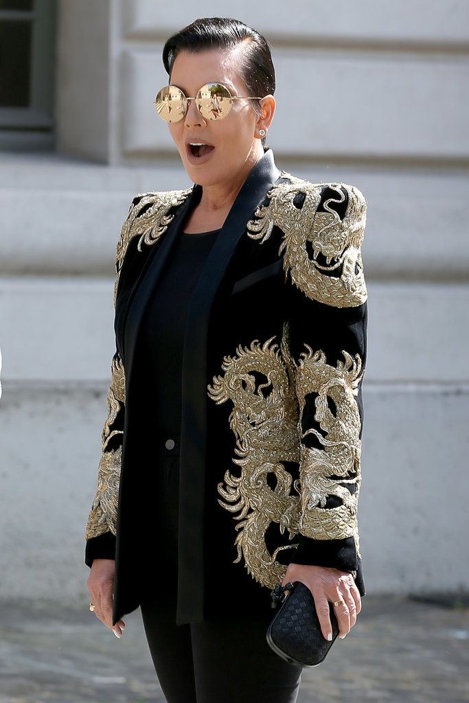 Kris Jenner wearing a gold dragon embroidered Balmain  tuxedo jacket and mirrored round gold sunglasses at Paris Fashion Week