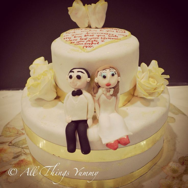 A #twotier #golden #anniversary #cake with a very special #message :) #bride #groom #goldandwhite #flowers #goldenflowers #weddingcake #figurines #bowtie #atyummy