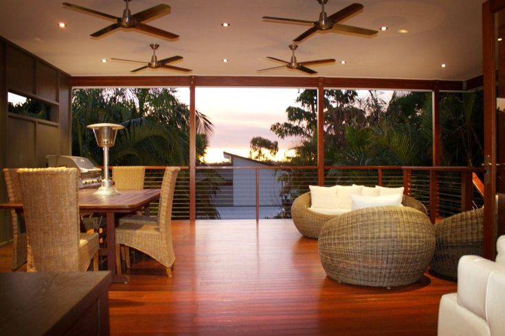 Modern Deck. Queensland, Australia.  This large deck offers the owners a fantastic space to entertain out of the harsh Queensland sun.  There is plenty of space for furniture and a bbq.  Downlights & 4 ceiling fans make sure that the deck is usable all day and night. Hardwood balustrade & stainless steel cables provide a modern touch. www.empiredesigns.com.au