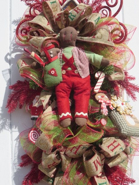 Gingerbread Swag Wreath, Christmas Door Wreath, Gingerbread Christmas Wreath for Front Door, Gingerbread Christmas Wreath, Christmas Swag  This fun whimsical Christmas gingerbread swag was created on a 30 evergreen swag. Taking center stage is a rustic, primitive Raz Imports plush gingerbread man with a brown fabric face, red trousers, red/tan checked vest, and green shirt. He is carrying a green sack filled with a rolling pin and gingerbread cookie man. A 5red and green plaid deco mesh…
