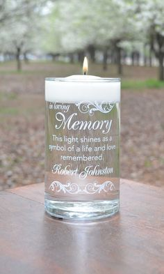 "Memorial Candle - ""This light shines as a symbol of a life and a love remembered.""  Permanently painted on the glass in your choice of ink color.  This ink color is Here Comes the Bride White. Perfect for remembering someone special anytime and anywhere. You personalize by choosing the permanent ink color and the names printed. We can also print a second line under the name for a special message or dates."