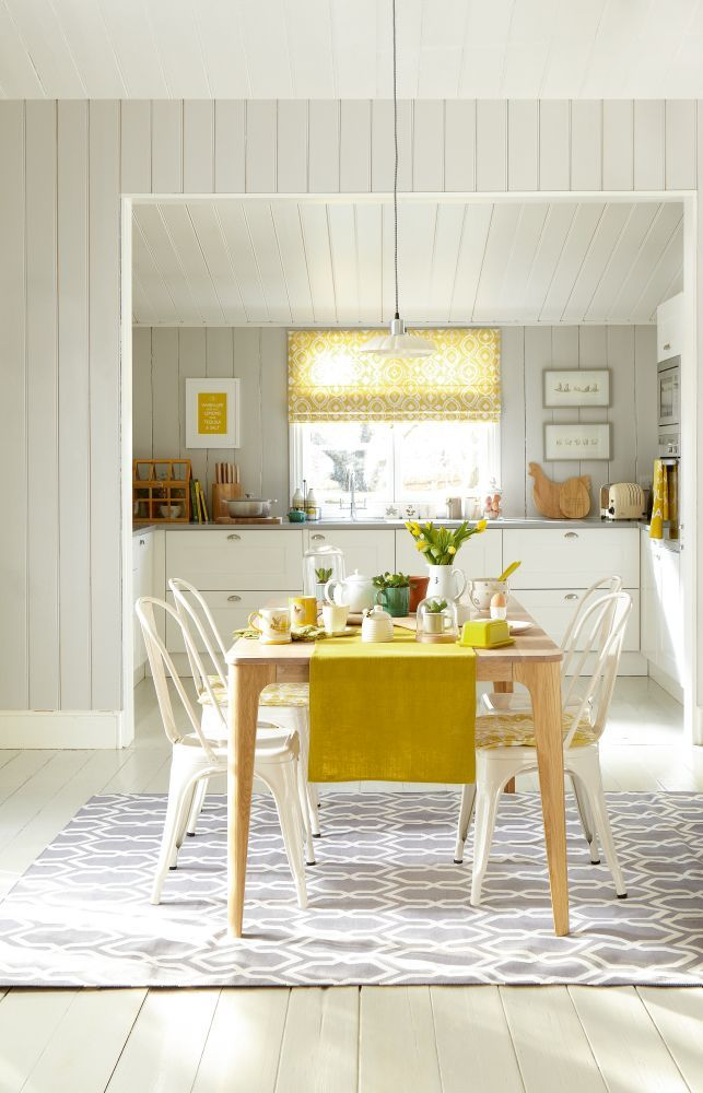 A clean, white kitchen is given another dimension with zesty yellow accessories and table linens. Photography: Mark Scott