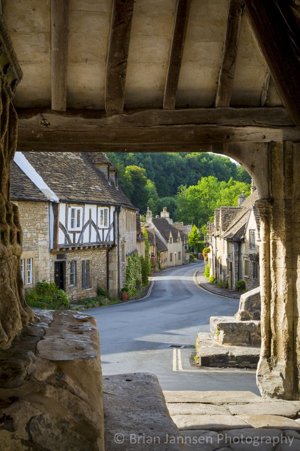 View through Market Cross Monument in Castle Combe, the Cotswolds, Wiltshire, England.