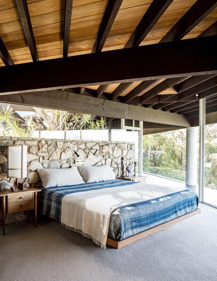 Le lit de la chambre principale, dessiné par Mark Haddawy, est entouré d'une paire de tables de nuit de Sam Maloof, d'une lampe de George Nakashima, de deux liseuses Arteluce et de statues africaines anciennes. Couvre-lits sont de Peter Dunham