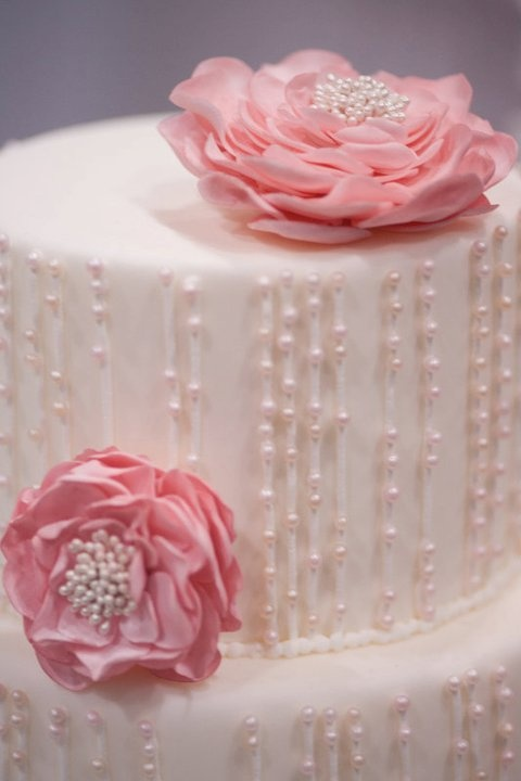 Ivory and Blush Pearls Drape this Beautiful White Wedding Cake with Handmade Pink Flowers