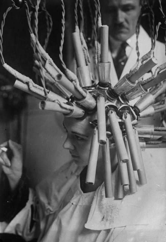 Keine Raketenmaschine, sondern ? ... ein Apparat zur Herstellung von Dauerwellen ! Eine Dame beim Ondulieren ihres Haares mittels eines Dauerwellen - Apparates. Die aus diese Weise hergestellten Dauerwellen halten ein Jahr.